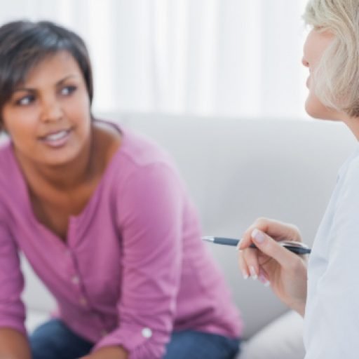 Therapist advising her smiling patient on couch in office